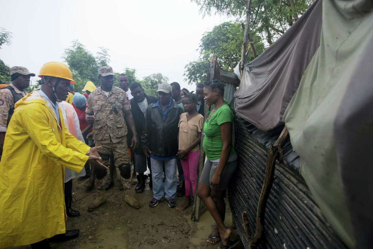 A civil protection worker, left, asks residents to evacuate the area near the Grise river, prior the arrival of Hurricane Matthew, in Tabarre, Haiti, Monday, Oct. 3, 2016. The center of Hurricane Matthew is expected to pass near or over southwestern Haiti on Tuesday, but the area is already experiencing rain from the outer bands of the storm. (AP Photo/Dieu Nalio Chery)