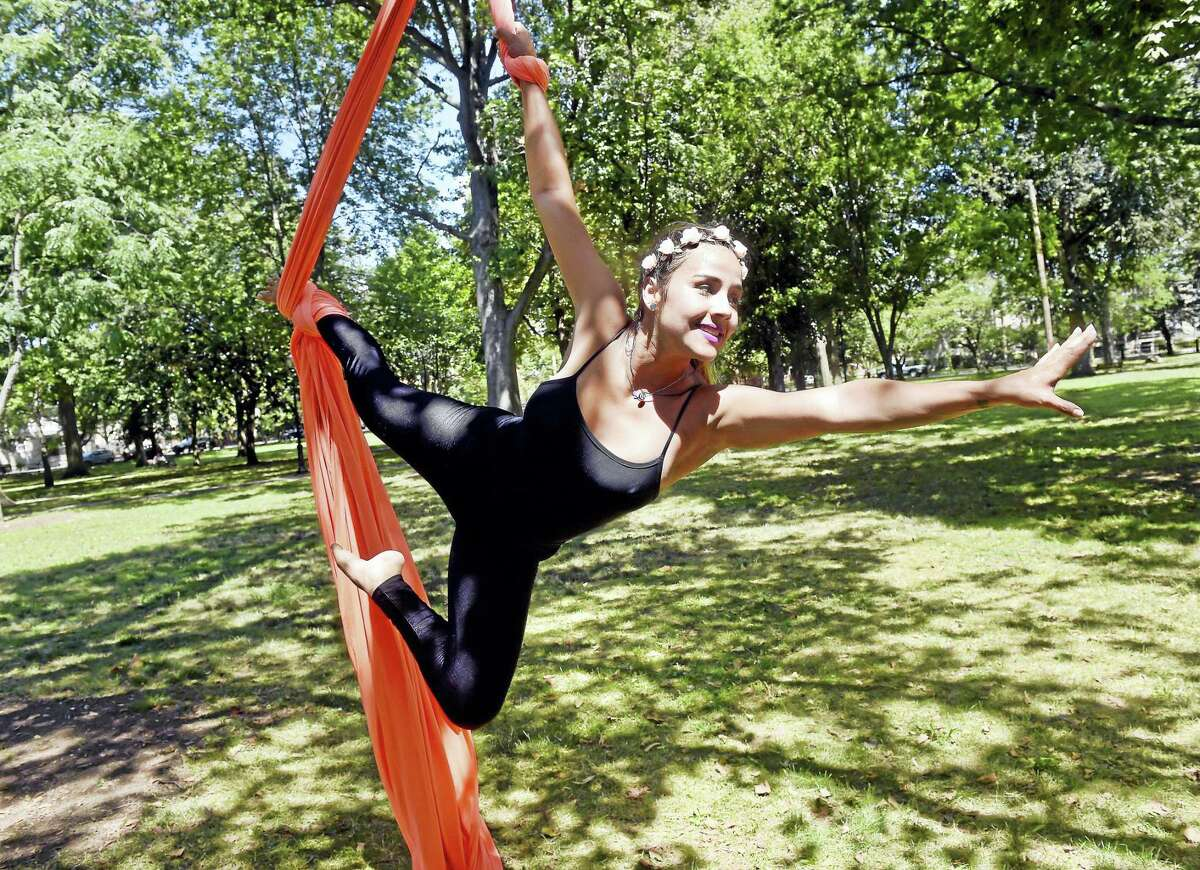 Carla Santana, owner of Aerial Silks Santa Elena, performs from a tree in Wooster Square in New Haven.