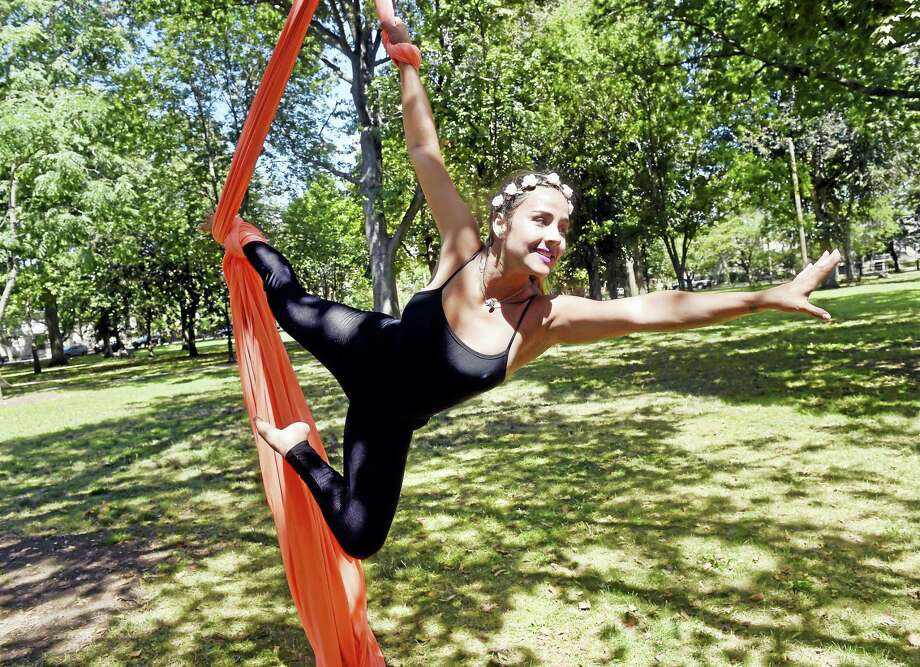 Carla Santana, owner of Aerial Silks Santa Elena, performs from a tree in Wooster Square in New Haven. Photo: Arnold Gold — New Haven Register