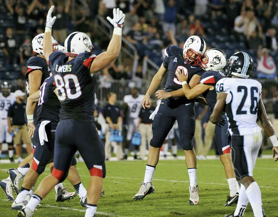 UConn's Bobby Puyol, second from right, embraces teammate Tyler Davis (9) after making a field goal to give UConn a 24-21 lead over Maine late in Thursday's game. Photo: Jessica Hill — The Associated Press   / AP2016