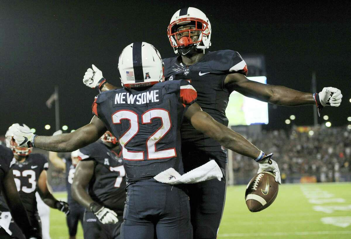 UConn's Arkeel Newsome (22) and Hergy Mayala bump chests after Newsome scored a touchdown in the second half.