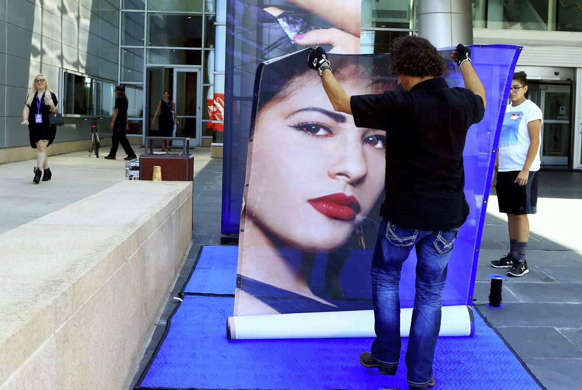 A worker from the Production Resource Group unrolls a large photo of the late singer Selena Quintanilla for the unveiling of the MAC Selena makeup collection on Sept. 29, 2016 at the American Bank Center in Corpus Christi, Texas. Known simply as Selena, the Mexican-American queen of Tejano music was shot to death in March 1995 by a former employee.