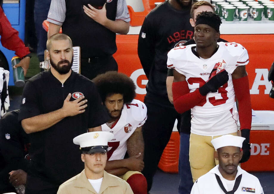 San Francisco 49ers quarterback Colin Kaepernick, middle, kneels during the national anthem before Thursday's game against the Chargers in San Diego. Photo: Chris Carlson — The Associated Press   / Copyright 2016 The Associated Press. All rights reserved.