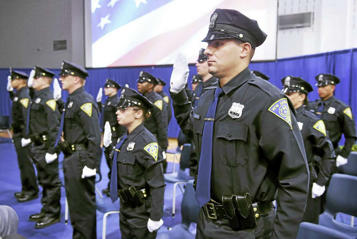 New Haven Police Officer Burr Allen and the rest of the New Haven Police Academy graduates take the oath of office during the New Haven Police Academy graduation ceremony Monday at Amistad High School.