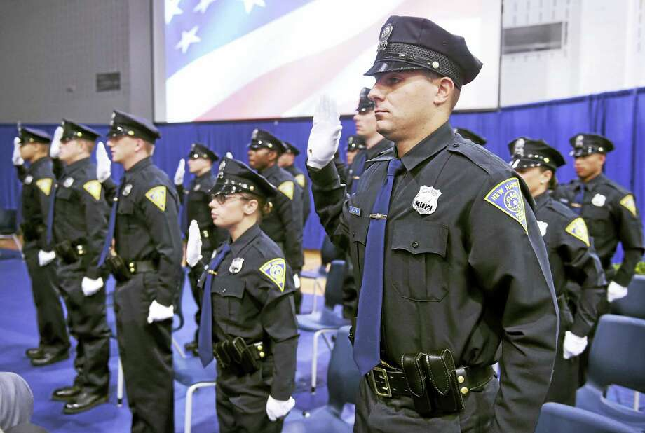 New Haven Police Officer Burr Allen and the rest of the New Haven Police Academy graduates take the oath of office during the New Haven Police Academy graduation ceremony Monday at Amistad High School. Photo: Arnold Gold — New Haven Register