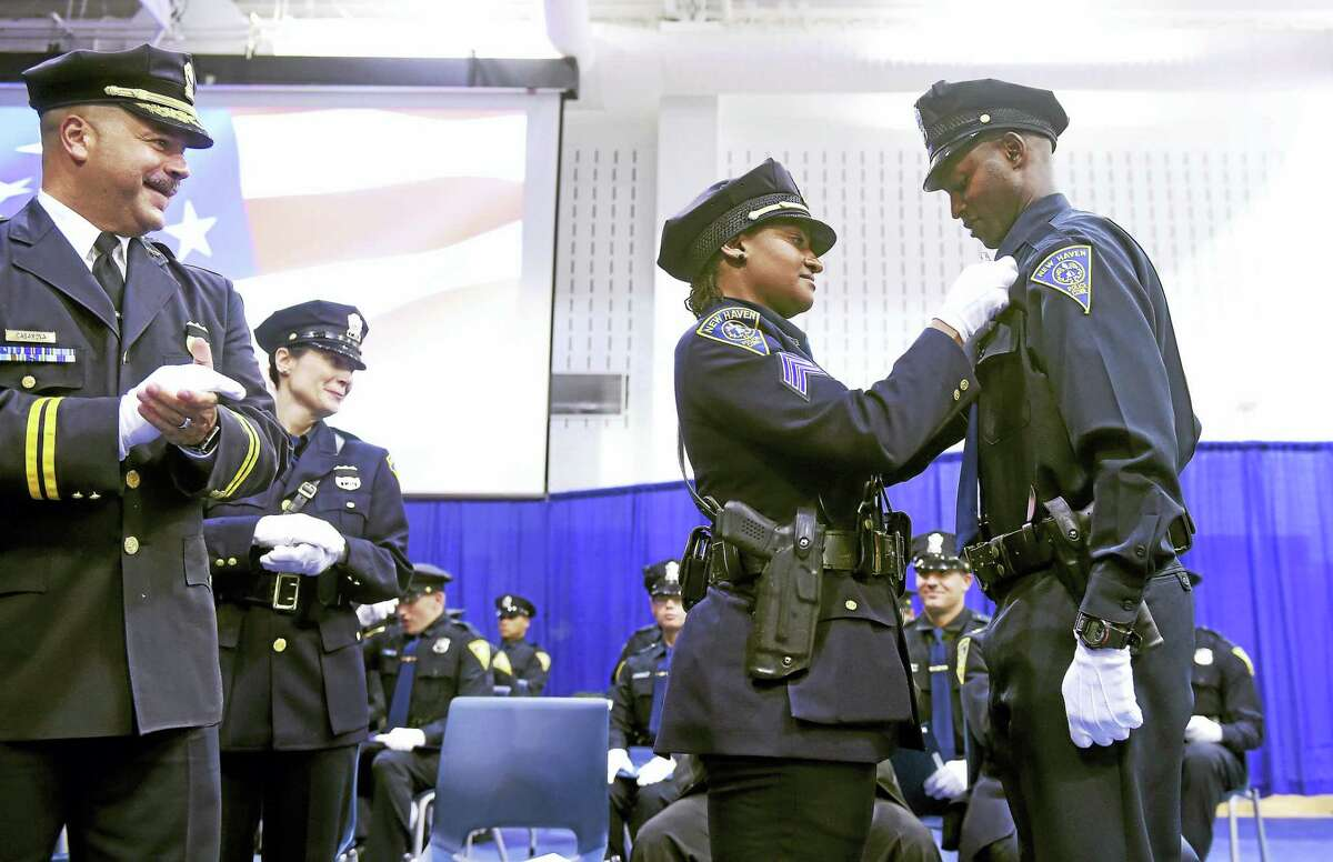 New Haven Assistant Chief Luis Casanova, left, watches New Haven Police Sgt. Tammi Means, center, pin the badge on her cousin, Officer Desmond Pittman, Monday.