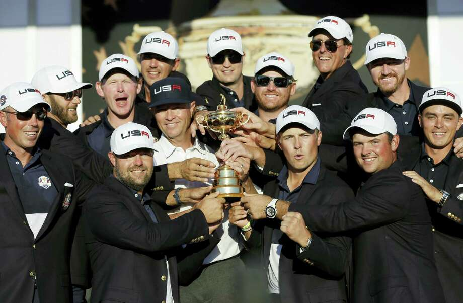 United States captain Davis Love III is surrounded by his players as they pose for a picture during the closing ceremony of the Ryder Cup on Sunday. Photo: David J. Phillip — The Associated Press   / Copyright 2016 The Associated Press. All rights reserved.