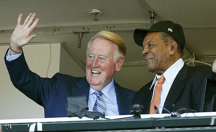 Los Angeles Dodgers announcer Vin Scully waves to fans alongside Hall of Famer Willie Mays during the fourth inning on Sunday. Photo: Tony Avelar — The Associated Press   / FR155217 AP