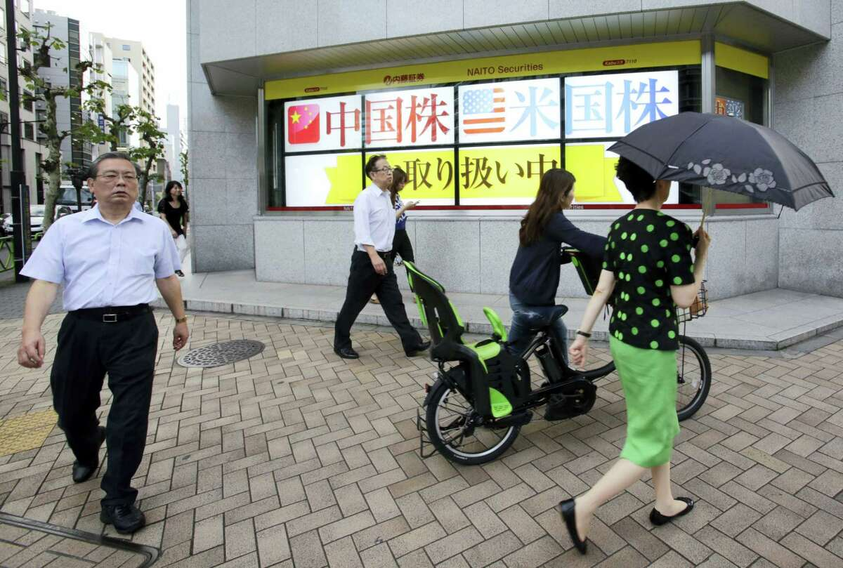 People walk past an electronic stock indicator of a securities firm in Tokyo, Monday. Shares were higher Monday in Asia, as investors shrugged off disappointing growth data from the U.S. and lackluster but better-than-expected manufacturing figures for China.