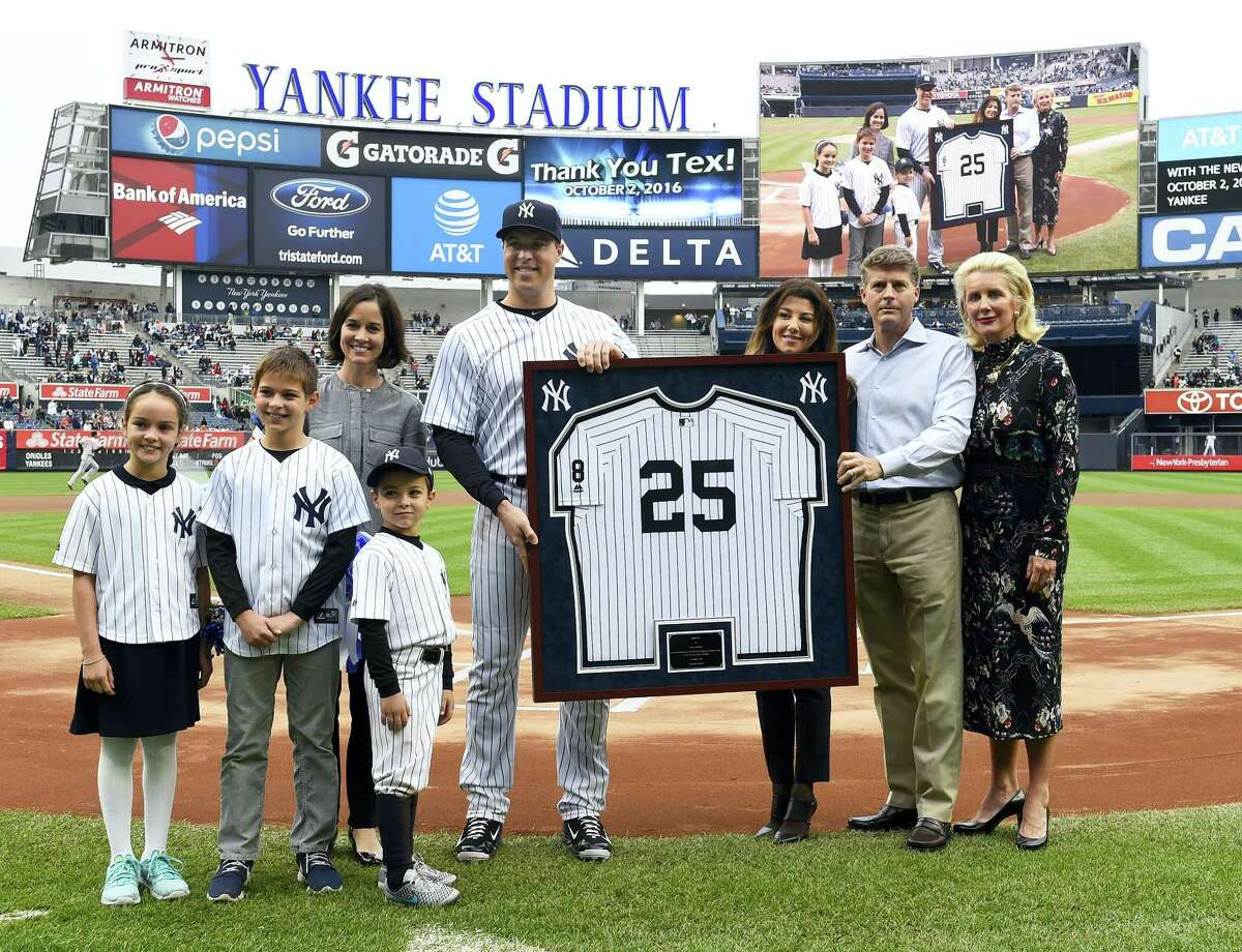 Yankees first baseman Mark Teixeira with his wife, Leigh, and children Jack, Addy and Will, stand with his framed jersey presented by Hal Steinbrenner and his wife, Christina DiTullio, left, and Jennifer Steinbrenner during a ceremony on Sunday.