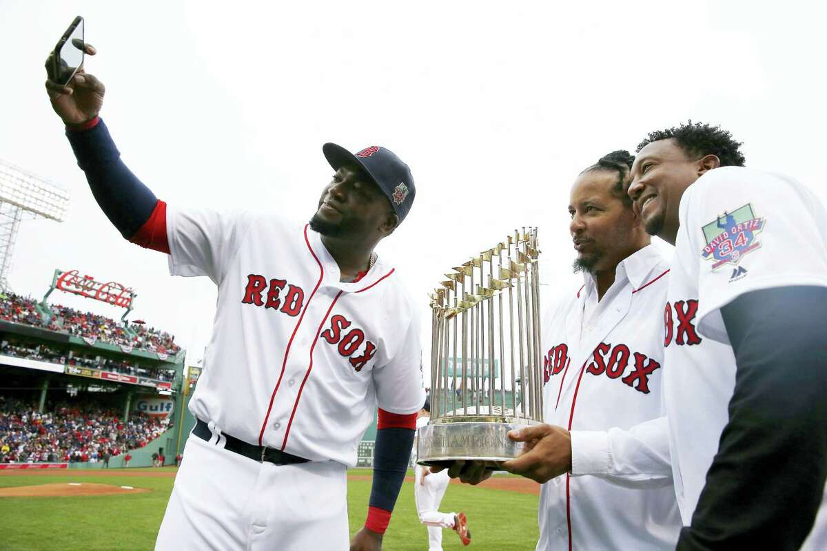 David Ortiz, left, takes a selfie with former teammates Manny Ramirez, center, and Pedro Martinez following a ceremony to honor Ortiz before Sunday's game.