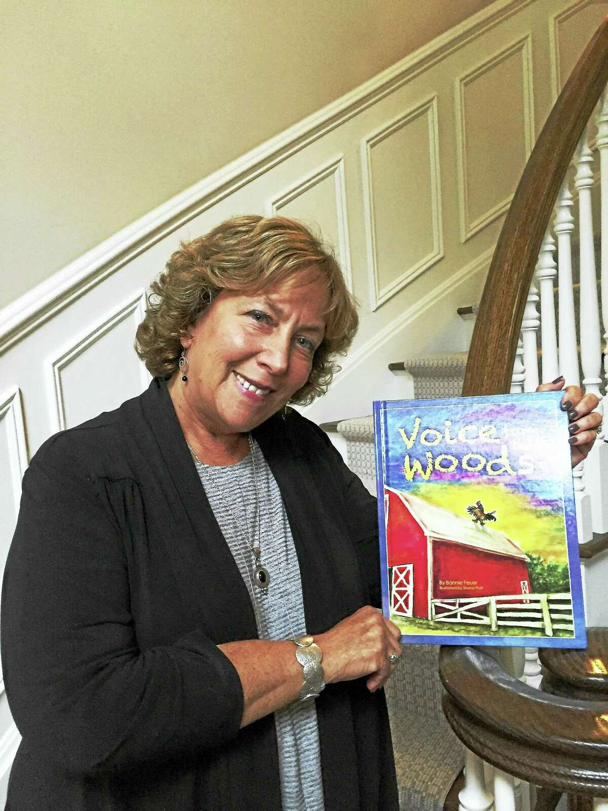 """Author and educator Bonnie Feuer with her newly released children's book, """"Voice from the Woods,"""" which addressed bullying through animal characters. (Contributed photo)"""