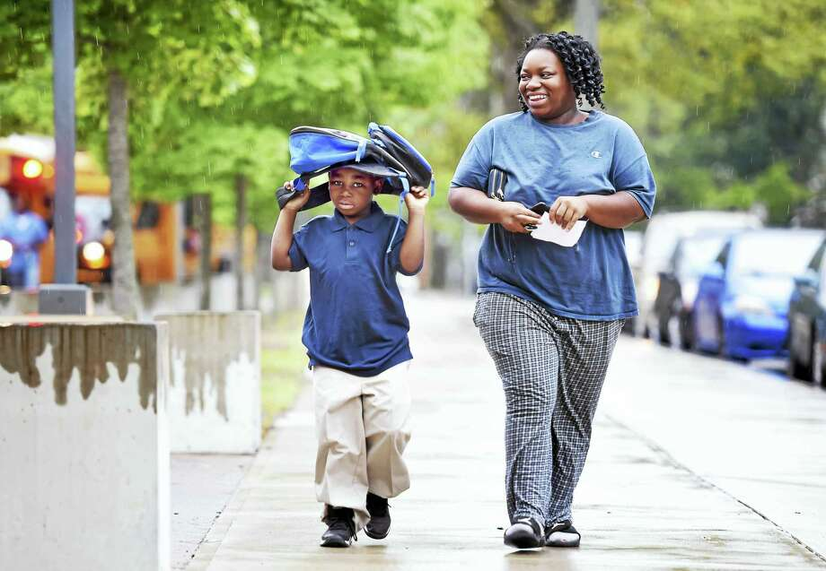First-grader Christopher Parker, 6, walks into East Rock School with his mother, Dashawna Garner, in New Haven on the first day of school Thursday. Photo: Arnold Gold — New Haven Register