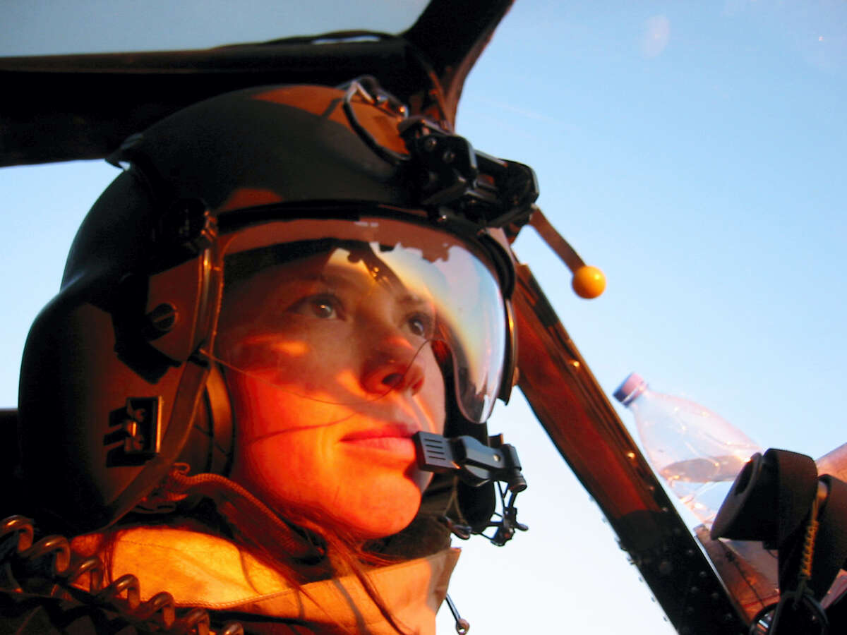 """In this 2005 photo provided by Mike Hambrecht, Chief Warrant Officer 2nd Class Amber Smith pilots a Kiowa Warrior helicopter during a sunrise mission in the Diyala province of Iraq. """"We live in a country that provides equal opportunities for men and women,"""" Smith contends. """"I'm an example of that — I wanted to be an air mission commander based on my own merits and skill level, not because of my gender."""""""