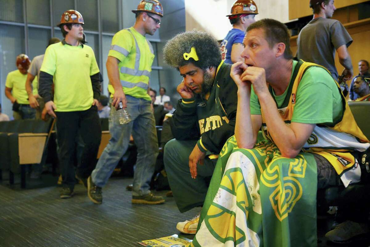 In this May 2, 2016 photo, Seattle SuperSonics fans Kris Brannon, center, and Kenneth Knutsen react to the Seattle City Council's 5-4 no vote against vacating stretch of road where investor Chris Hansen hopes to eventually build an arena that could house an NBA and NHL team. Five women on Seattle's City Council outvoted four men to derail the sports arena project.