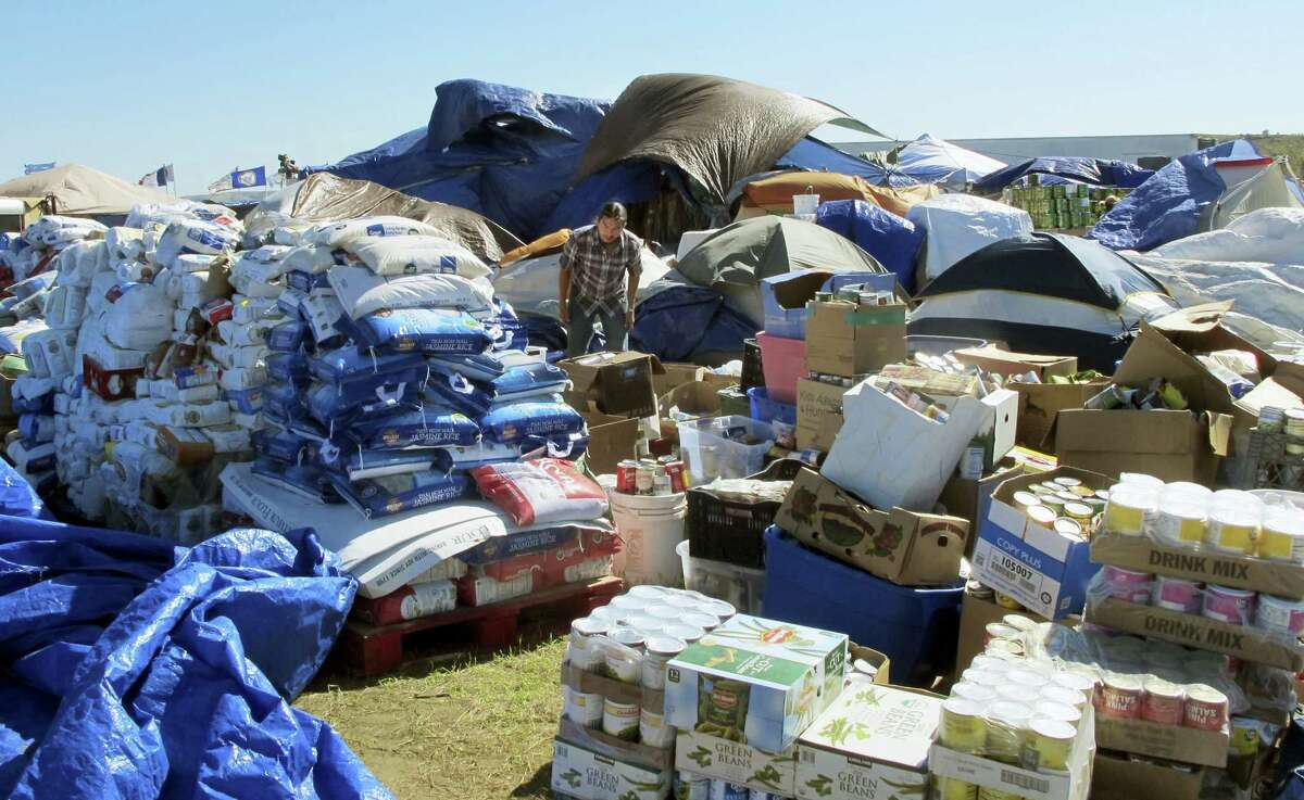 In this Sept. 14, 2016 photo, a volunteer sorts through donated food near the Standing Rock Sioux Reservation in North Dakota. The sprawling encampment that's a protest against the four-state Dakota Access oil pipeline has most everything it needs to be self-sustaining — except a federal permit to be there.