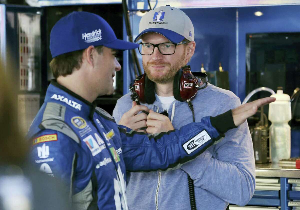 Dale Earnhardt Jr., right, listens to Jeff Gordon as they stand in the garage area before practice for Sunday's race at Dover International Speedway.