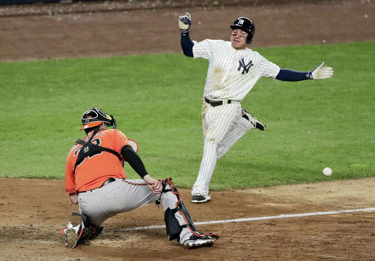 The Yankees' Ronald Torreyes, right, looks to score as Orioles catcher Matt Wieters waits for the throw on Saturday.