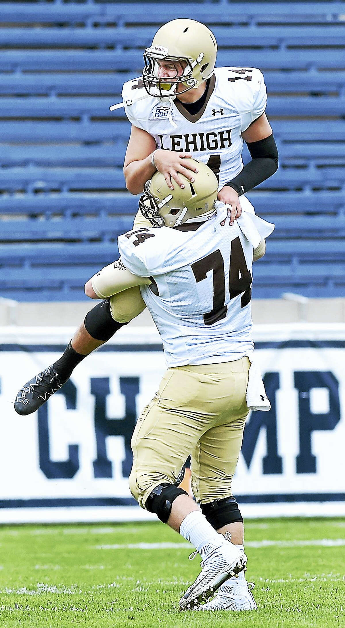 Lehigh quarterback Brad Mayes, top, celebrates with Brandon Short after Lehigh scored in the first half Saturday at Yale Bowl.
