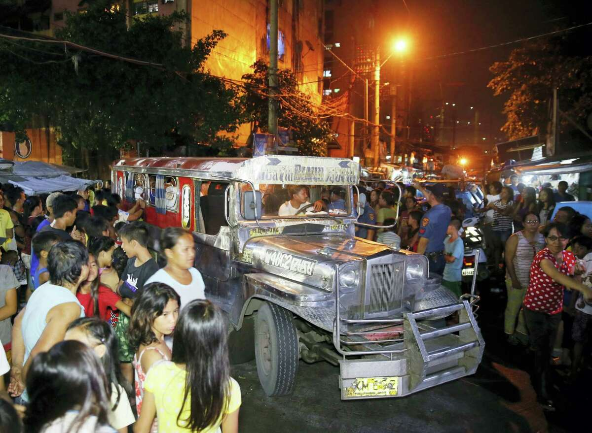 """Residents and relatives gather around a vehicle wherein rounded up males prepare to be transported to a police station in the continuing """"War on Drugs"""" campaign of President Rodrigo Duterte at slum community of Tondo in Manila, Philippines late Friday, Sept. 30, 2016. Duterte raised his bloody anti-crime war rhetoric to a new level Friday, comparing it to how Hitler massacred millions of Jews and saying how he would be """"happy to slaughter"""" 3 million addicts. Duterte issued his latest threat against drug dealers and users early Friday on returning to his home in southern Davao city after visiting Vietnam, where he discussed his anti-drug campaign with Vietnamese leaders."""