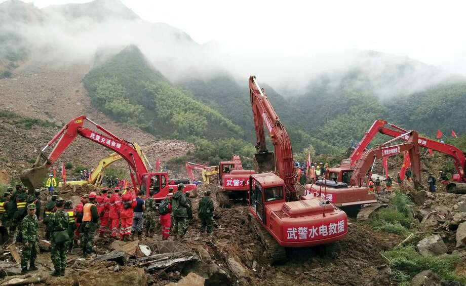 Rescuers use heavy equipment to search for people missing after a landslide in Sucun village in eastern China's Zhejiang province Friday, Sept. 30, 2016. Several people are reported dead and more are still missing after two landslides triggered by a major typhoon swept through separate villages in southeastern China, state media reported. Photo: Chinatopix Via AP    / Chinatopix