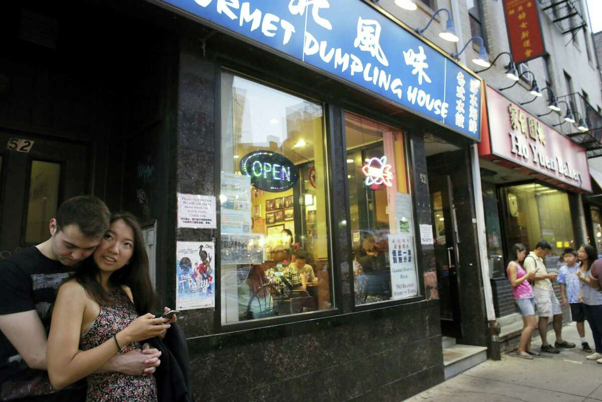 A couple waits outside a restaurant in Boston's Chinatown neighborhood.