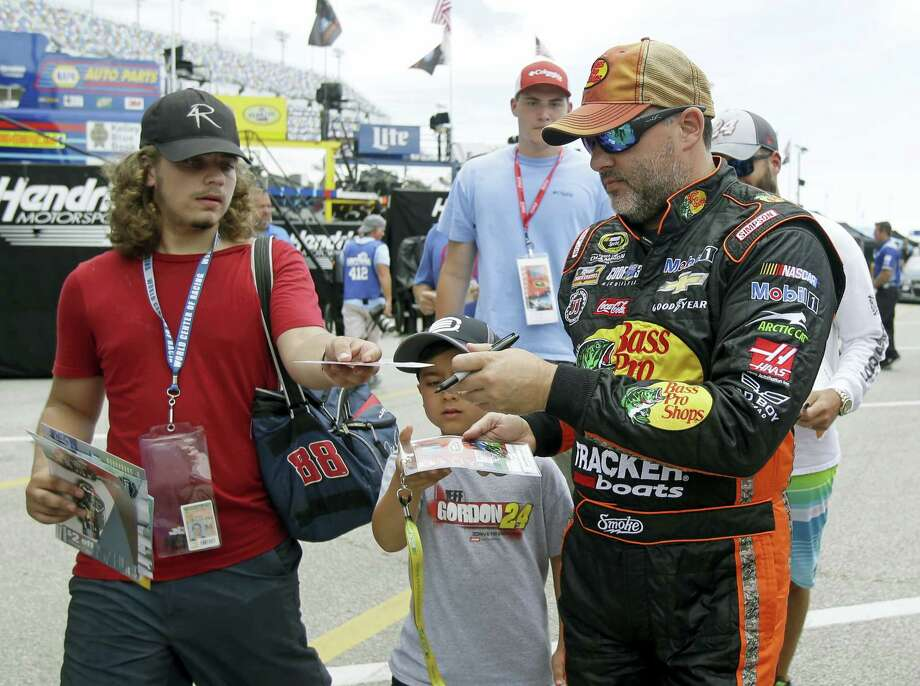 Tony Stewart, right, signs autographs during practice at Daytona International Speedway on Thursday. Photo: John Raoux — The Associated Press   / Copyright 2016 The Associated Press. All rights reserved. This material may not be published, broadcast, rewritten or redistribu
