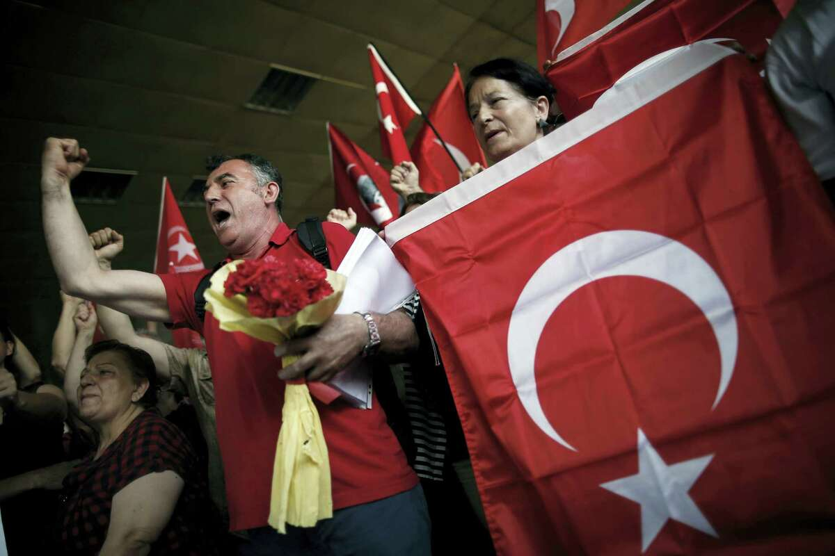 Colleagues shout slogans to condemn terrorism as they stage a memorial ceremony for Erol Eskisoy and Ali Zulfukar Yorulmaz, two taxi drivers killed in Tuesday blasts at the entrance of Ataturk Airport in Istanbul, Thursday, June 30, 2016. A senior Turkish official on Thursday identified the Istanbul airport attackers as a Russian, Uzbek and Kyrgyz national hours after police carried out sweeping raids across the city looking for Islamic State suspects.