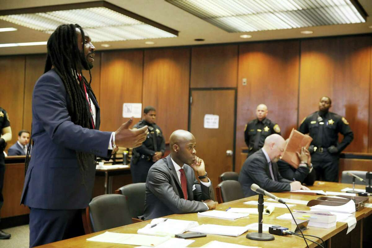 As defendant Shawn Custis, second right, hides his face with a folder while sitting in court, Essex County Assistant Prosecutor Jamel Semper, left, asks that he be given a life sentence for the brutal beating of a woman, Wednesday, June 29, 2016, in Newark, N.J. Custis was sentenced to life plus 5 years by Superior Court Judge Ronald Wigler for the brutal beating of a woman during a 2013 home invasion caught on a nanny-cam home security video.