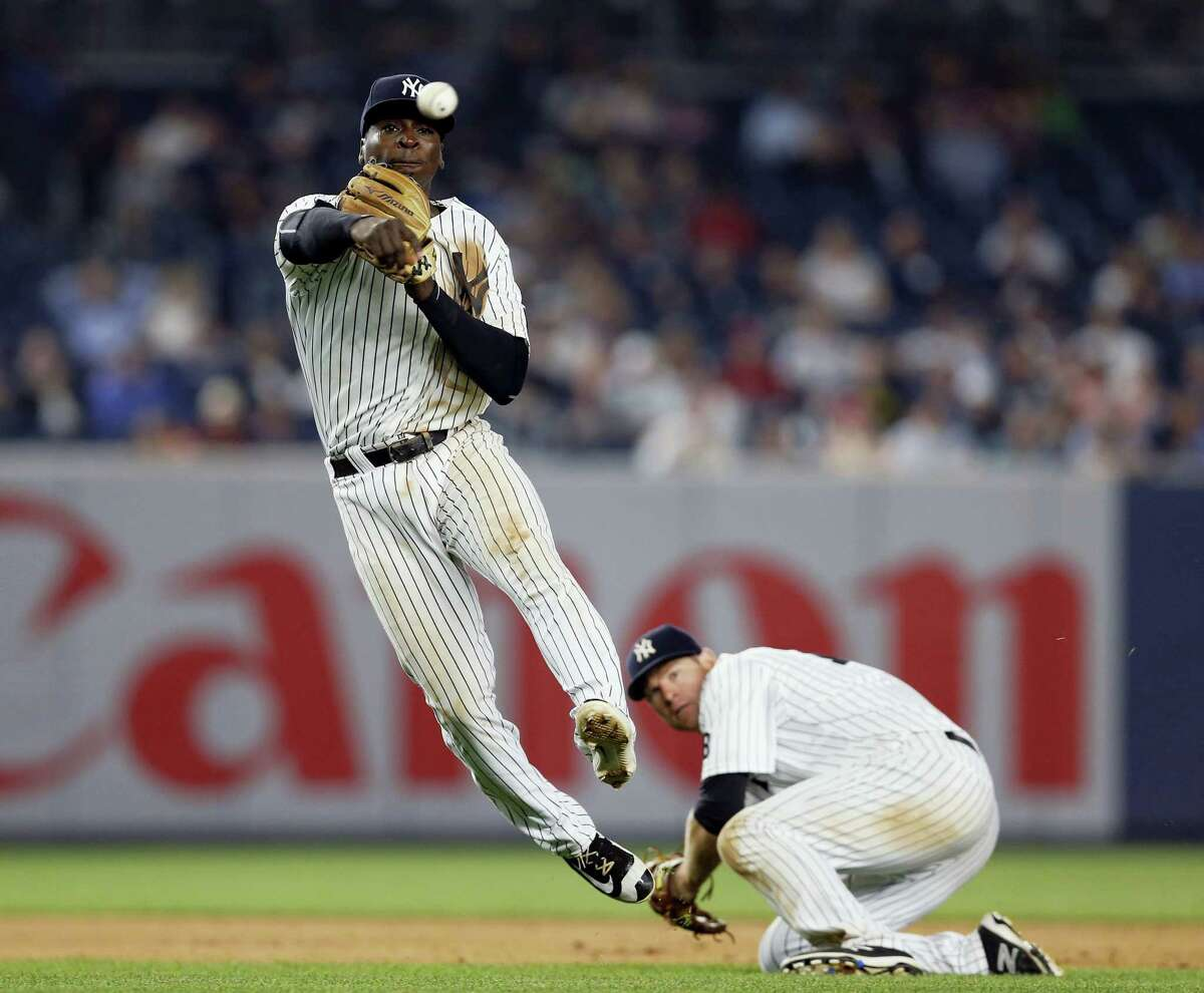 New York Yankees third baseman Chase Headley crouches as shortstop Didi Gregorius throws to first trying to put out Texas Rangers' Jurickson Profar during the eighth inning of a baseball game in New York, Tuesday, June 28, 2016. Proffer reached on an infield single. The Rangers won 7-1.