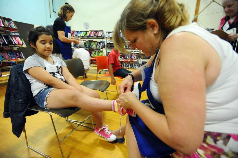 Keelyn Castro tries on shoes during the 2nd annual Back to School Shop, which provides low-income students with the chance to select new clothes, school supplies and a backpack at no cost to the family, at Davenport Ridge Elementary School on Sunday, July 31, 2016. Photo: Michael Cummo / Hearst Connecticut Media / Stamford Advocate
