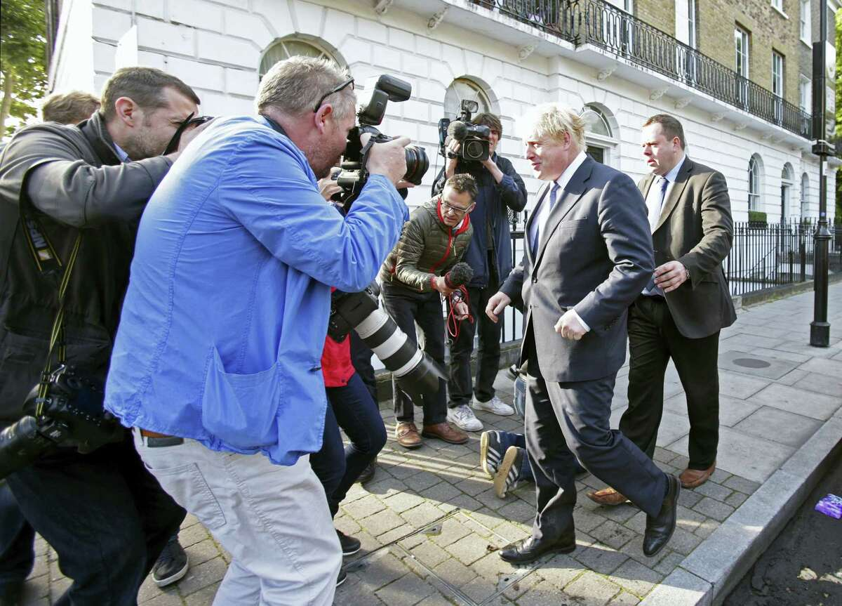 """Former London mayor and prominent """"Vote Leave"""" campaigner Boris Johnson, center, leaves his home in north London, surrounded by the media Tuesday."""