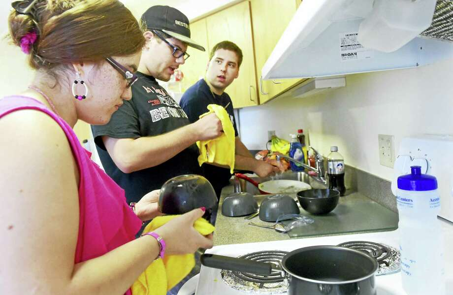 Julitza Lopez, 19, Jonathan, Meyers, 18, and Brent Bouteiller, 20, wash and dry dishes together in a common area of a dormitory at Quinnipiac University Tuesday during the Quinnipac University Summer Life Program. Photo: Peter Hvizdak — New Haven Register   / ?2016 Peter Hvizdak