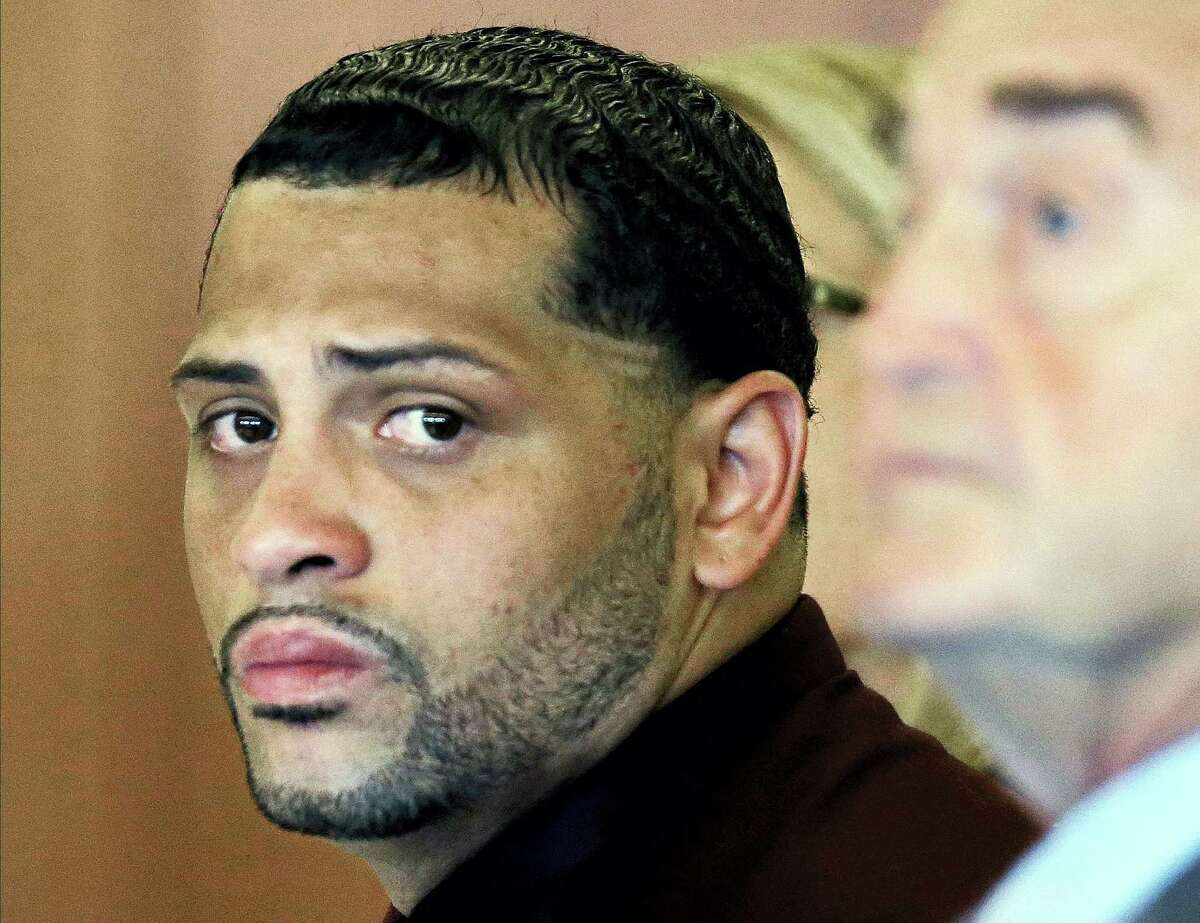 In this 2015 file photo, Carlos Ortiz, co-defendant of former New England Patriots player Aaron Hernandez, sits with his defense attorney John Connors.