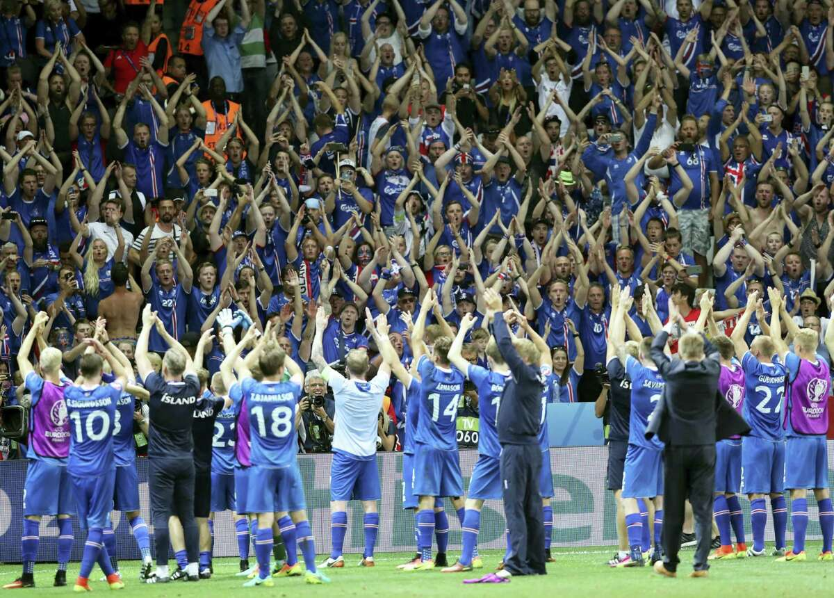 Iceland players celebrate with their supporters after beating England on Monday.