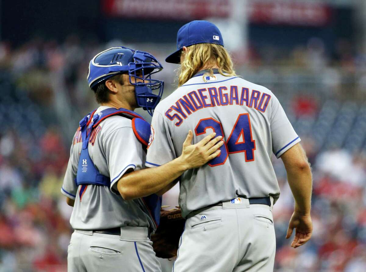 Travis d'Arnaud, left, talks with Syndergaard during the first inning.