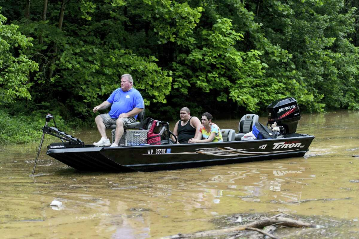 Doug May steers his boat across Frame Road, which was partially flooded, after rescuing Shawn Berry and Darcy Cochran from a parking lot in Elkview, W.Va., Friday, June 24, 2016.