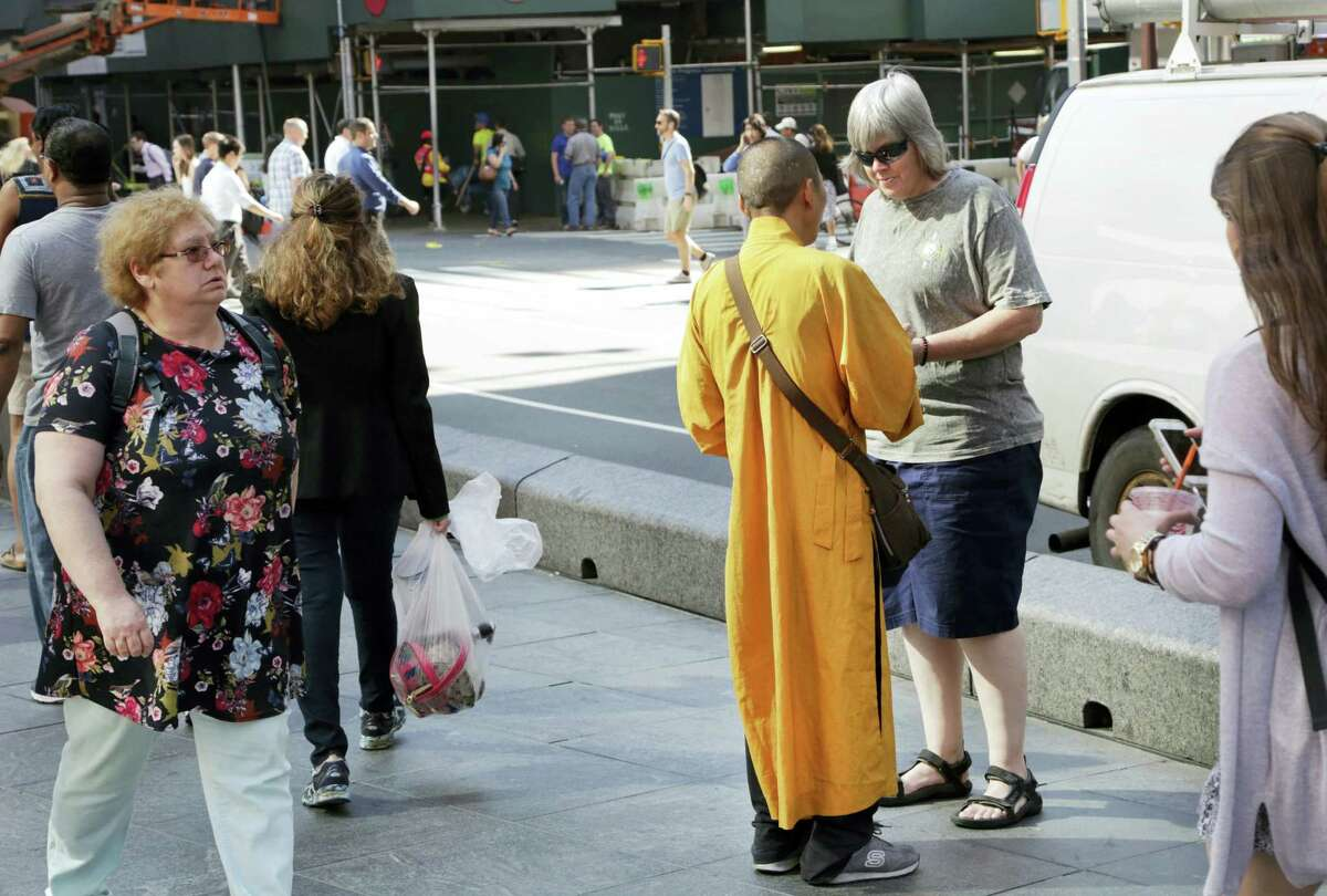 In this Friday, June 24, 2016, photo, a man wearing an orange robe talks with a woman in New York's Times Square. They wear orange robes and carry shiny medallions, stopping people in New York City to offer greetings of peace. The men identify themselves as Buddhist monks and solicit donations for a temple in Thailand. But the Buddhist Council of New York says the men are 'Äúfake monks'Äù who are not affiliated with any known temple and are just looking to make a quick buck.