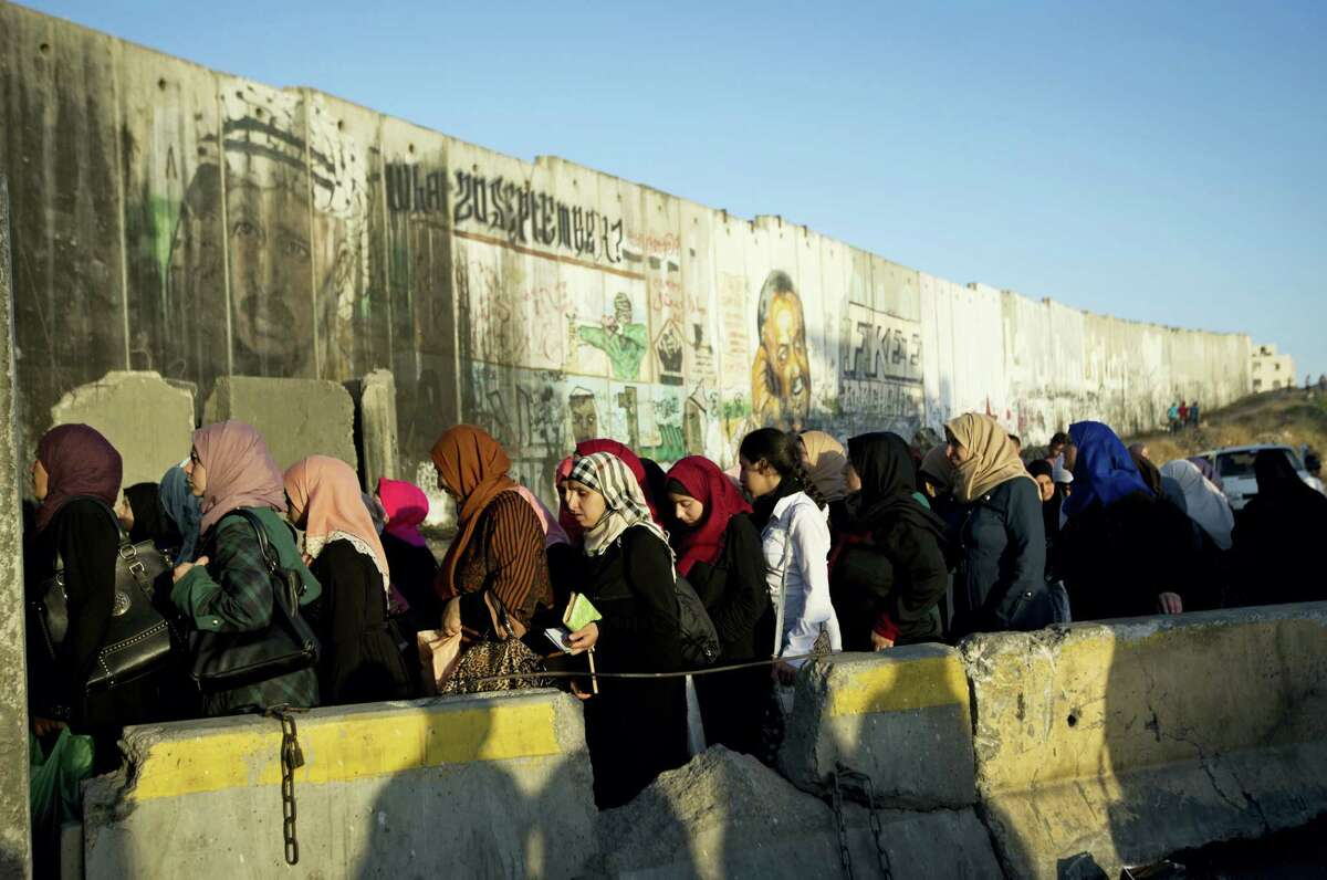 Palestinian women walk past a section of Israel's separation barrier to cross the checkpoint on their way to attend the third Friday prayers in Jerusalem's al-Aqsa mosque during Muslim holy month of Ramadan, at the Qalandia checkpoint between the West Bank city of Ramallah and Jerusalem, Friday, June 24, 2016.