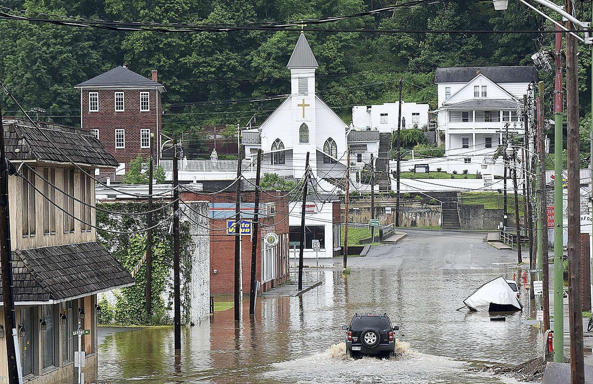 A vehicle makes a wake along the flooded Lower Oakford Ave. Friday, June 24, 2016, in Richwood, W.Va.