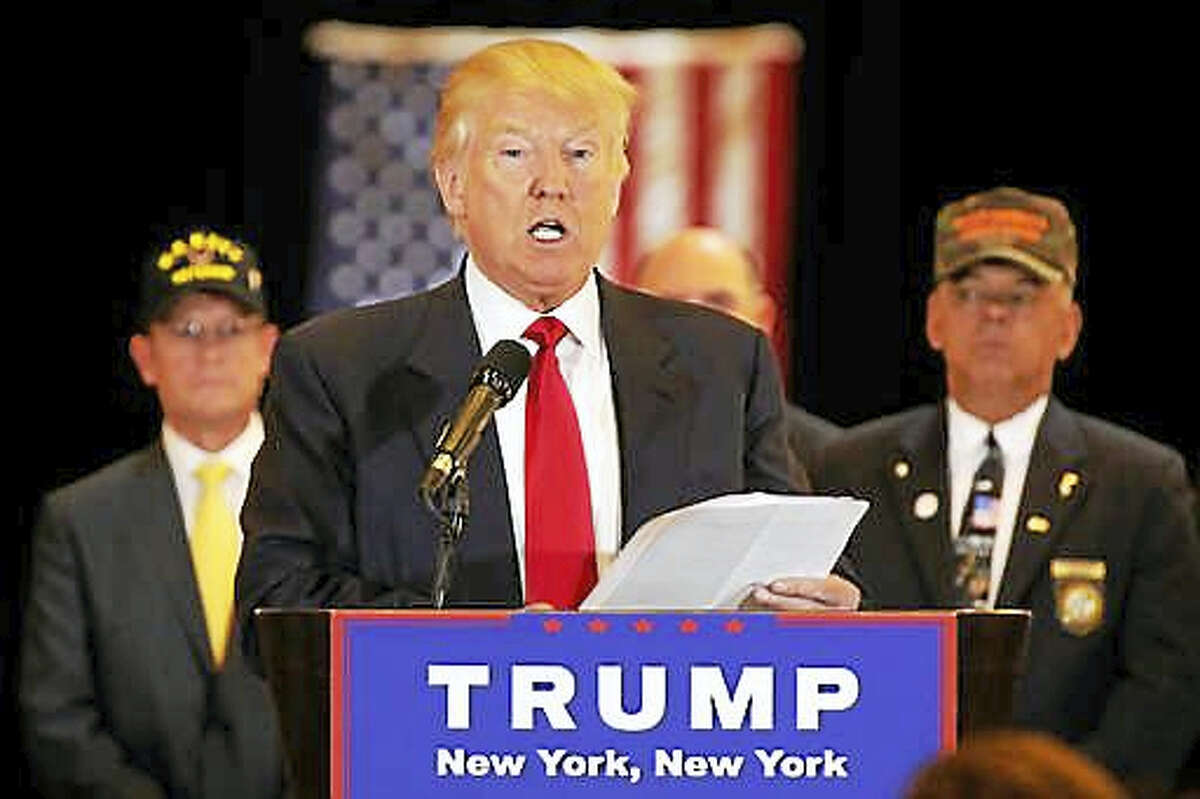 Republican presidential candidate Donald Trump reads from a list of donations to veteran's groups, during a news conference in New York, Tuesday, May 31, 2016.