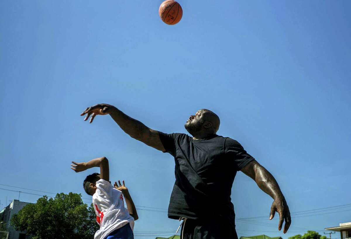 Shaquille O'Neal plays with a youngster during a clinic in Havana on Sunday.