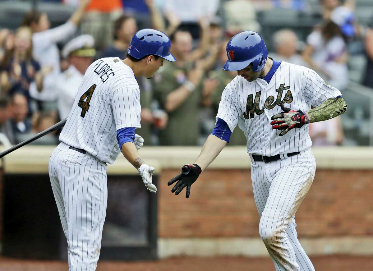 Neil Walker, right, is greeted by Wilmer Flores after hitting a solo home run during the seventh inning for the Mets against the White Sox.