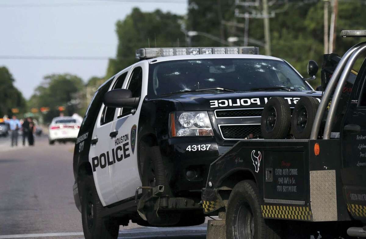 A Houston Police Deptartment vehicle hit many times by gunfire is removed from the area Sunday, May 29, 2016, in Houston. A man came into a Houston auto detail shop and began shooting, killing a man known to be a customer and putting a neighborhood on lockdown before being killed by a SWAT officer, police said. Several people were shot and injured,