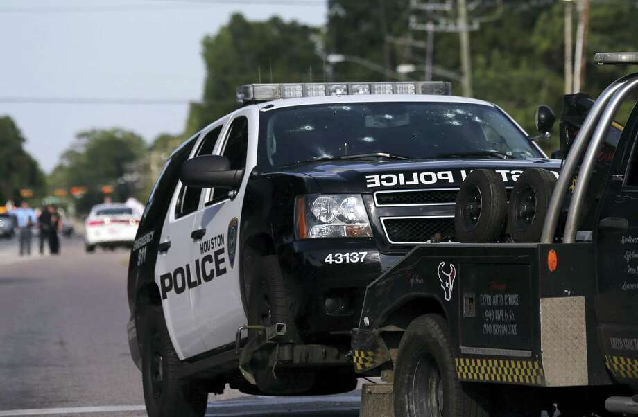 A Houston Police Deptartment vehicle hit many times by gunfire is removed from the area Sunday, May 29, 2016, in Houston. A man came into a Houston auto detail shop and began shooting, killing a man known to be a customer and putting a neighborhood on lockdown before being killed by a SWAT officer, police said. Several people were shot and injured, Photo: Elizabeth Conley/Houston Chronicle Via AP    / Houston Chronicle