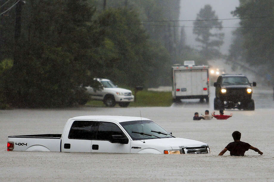 A man, foreground, checks to make sure everyone made it safely out of a truck that flooded when the three men in the background drove around a closed road barrier along Nichols Sawmill Road and lost control of the vehicle in rising flood water Friday, May 27, 2016 in Magnolia, Texas. Photo: Michael Ciaglo/Houston Chronicle Via AP    / Houston Chronicle
