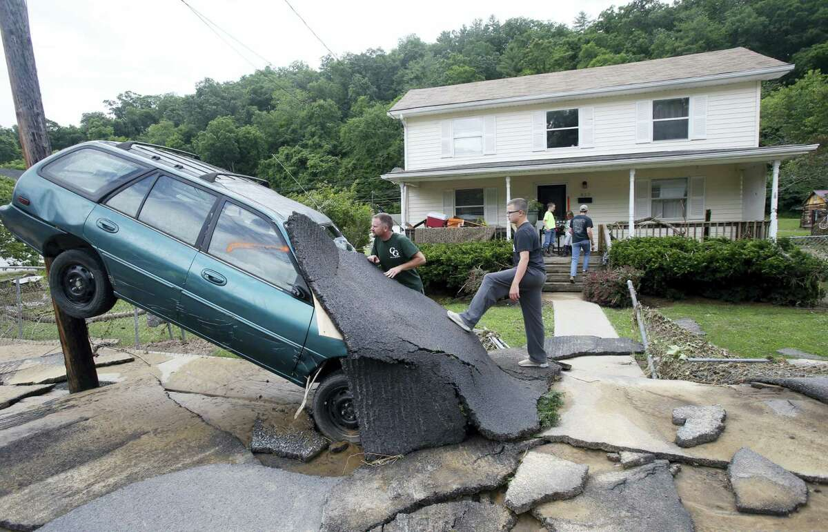 Jay Bennett, left, and step-son Easton Phillips survey the damage to a neighbors car in front of their home damaged by floodwaters as the cleanup begins from severe flooding in White Sulphur Springs, W. Va. on June 24, 2016. A deluge of 9 inches of rain on parts of West Virginia destroyed or damaged more than 100 homes and knocked out power to tens of thousands of homes and businesses.