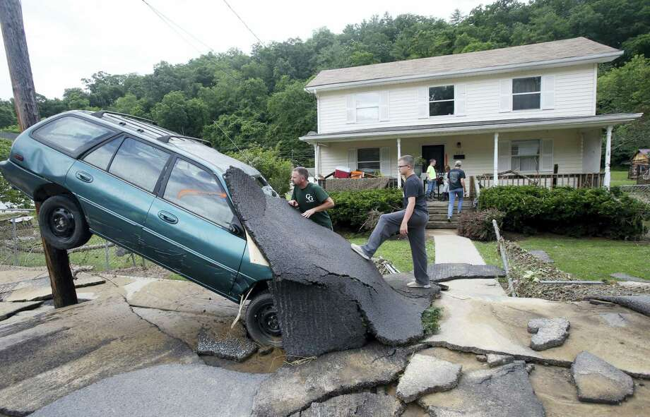 Jay Bennett, left, and step-son Easton Phillips survey the damage to a neighbors car in front of their home damaged by floodwaters as the cleanup begins from severe flooding in White Sulphur Springs, W. Va. on June 24, 2016. A deluge of 9 inches of rain on parts of West Virginia destroyed or damaged more than 100 homes and knocked out power to tens of thousands of homes and businesses. Photo: AP Photo/Steve Helber   / AP