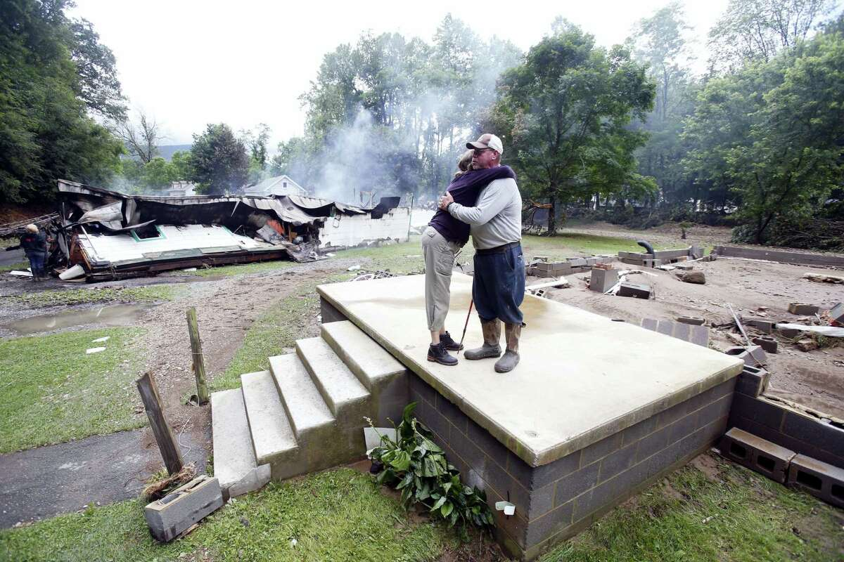 Jimmy Scott gets a hug from Anna May Watson, left, as they clean up from severe flooding in White Sulphur Springs, W. Va. on June 24, 2016.