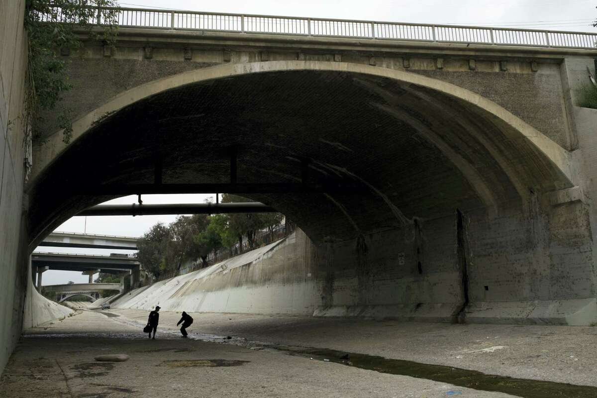 In this Monday, May 16, 2016, photo, two homeless men walk under the bridge along the Los Angeles River in Los Angeles, where almost extinct form of American hieroglyphics known as hobo graffiti were discovered.